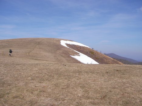 A hiker follows the Appalachian Trail across Max Patch Bald in Haywood County, NC.
