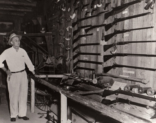 John B. Battle standing next to his collection of guns.