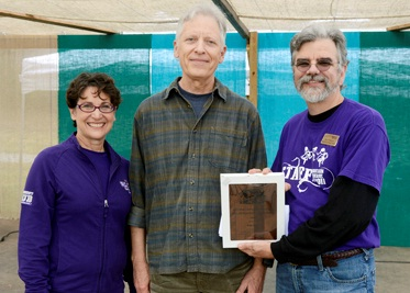 Rob Tiger (center) is congratulated by Susan Belcher, wife of WCU Chancellor David O. Belcher, and Scott Philyaw, director of WCU's Mountain Heritage Center.